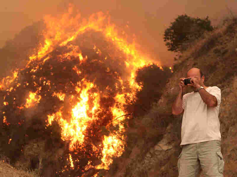 A resident of Tujunga, Calif. takes a photograph of a back fire that burns near his home Tuesday.