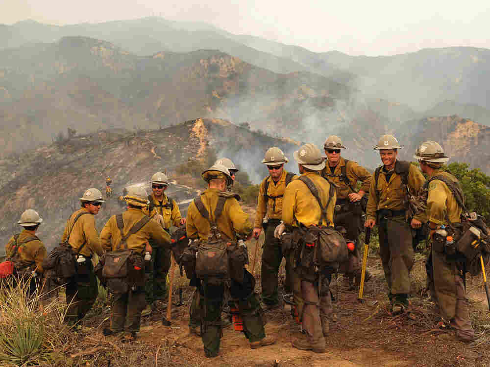 Firefighters take a break near the suburb of Glendale on the outskirts of Los Angeles.