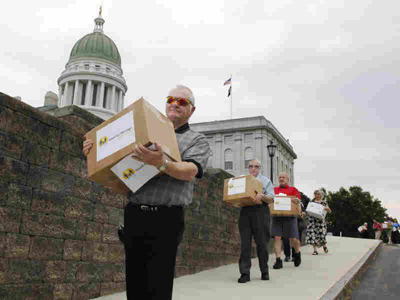 The Rev. Buddy Gough carries a box of signed petitions to the Maine secretary of state's office.