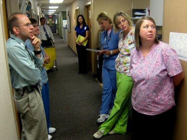 Dr. Dave Yehl (left) meets with nurses and a scheduler for a twice-a-day hallway huddle. Under the experimental payment scheme, the team is taking a more wellness-oriented approach. (NPR)