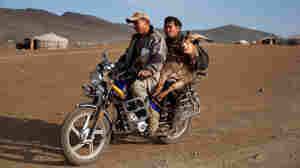 Ninja miners carry a ram by motorcycle through a gold mining camp in Mongolia.