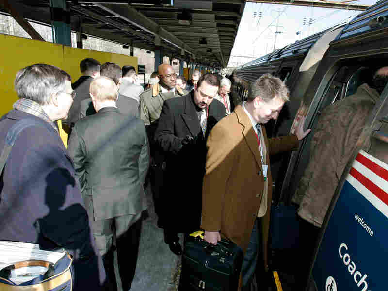 Workers board a train with briefcases