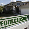 A foreclosure sign sits outside a home for sale in Phoenix, Feb. 17, 2009.