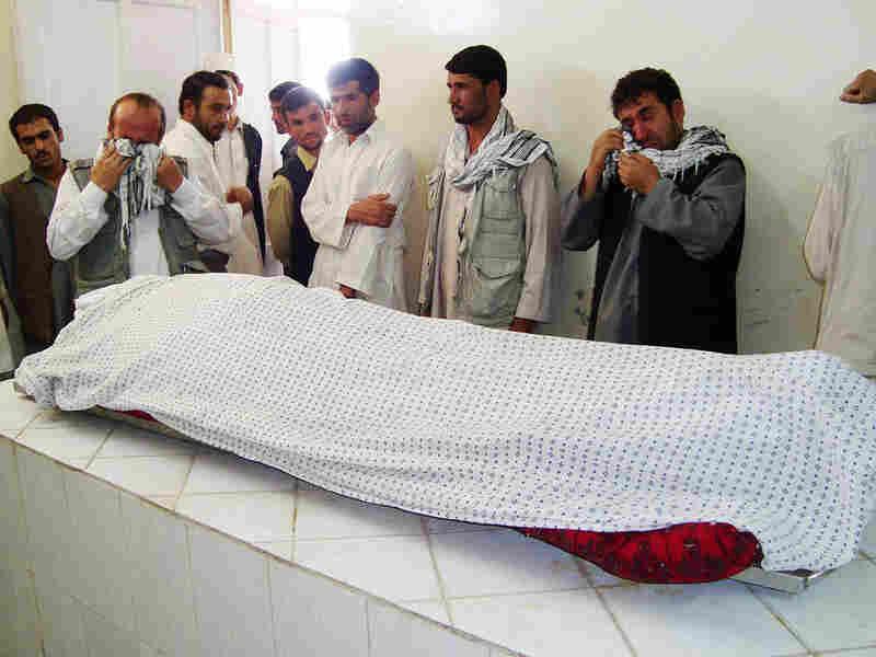 Men weep over the body of Afghan journalist  Sultan Munadi.