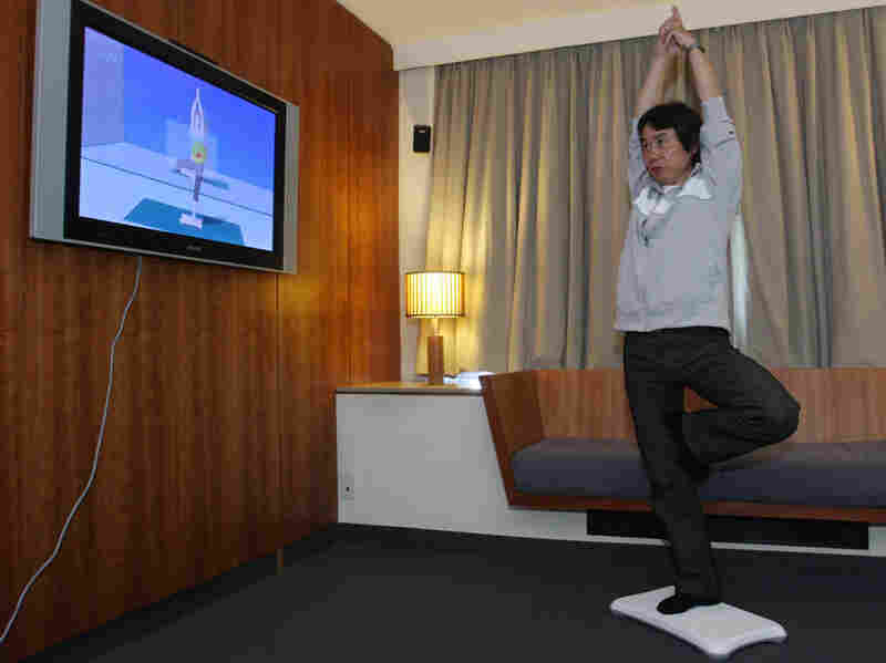 A Nintendo game designer demonstrates a yoga pose on the Wii.