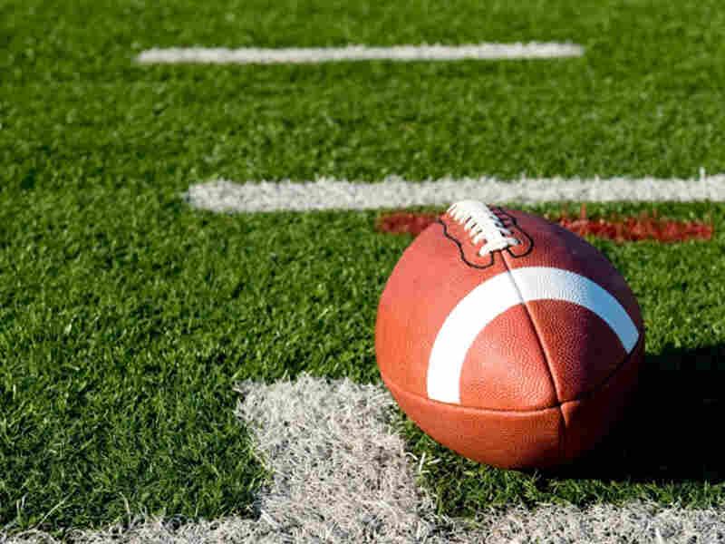 A football lies on an empty field.