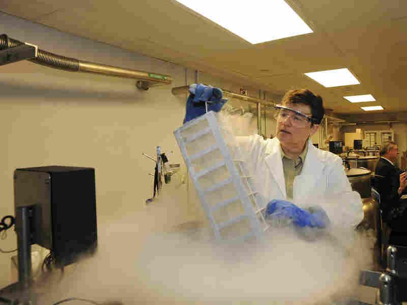 A researcher pulls samples from a nitrogen storage vat.