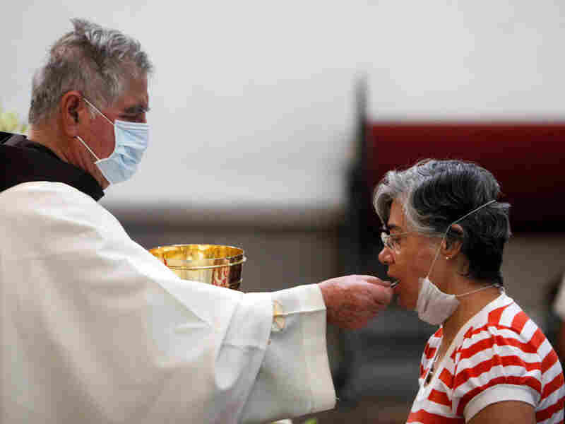 A priest, wearing a mask as a precaution against swine flu, gives Holy Communion to a parishioner