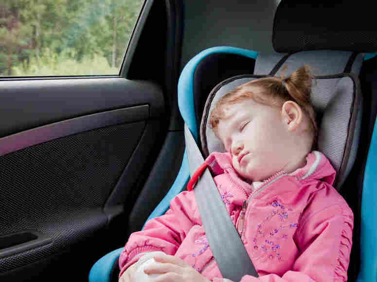 A child sleeps in a booster seat in the car.