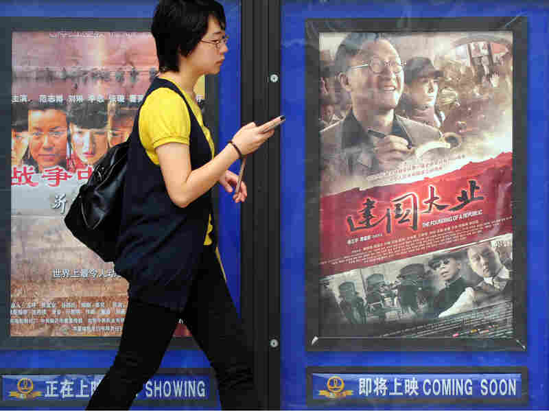 Woman walks past poster for 'The Founding Of A Republic' in Beijing