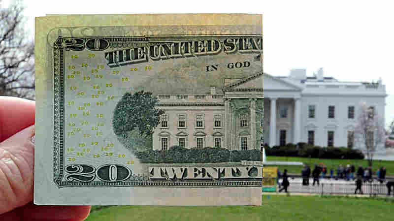 A photo illustration showing a U.S. $20 bill matched up to the White House.