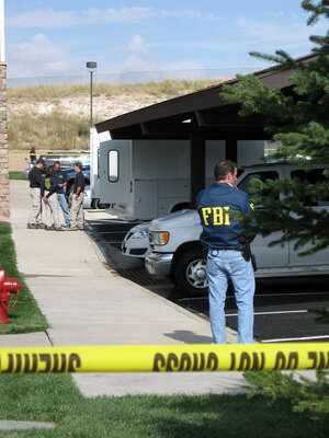 Federal agents stand outside the suburban Denver apartment building where Najibullah Zazi lives.