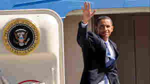 President Barack Obama waves from the doorway of Air Force One.