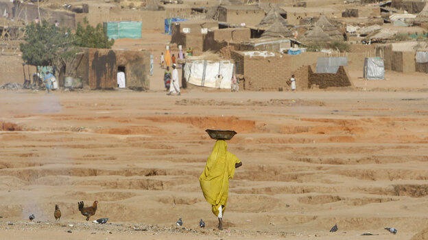 WIDE: A Sudanese refugee woman carries food supplies at the Abu Shouk refugee ca