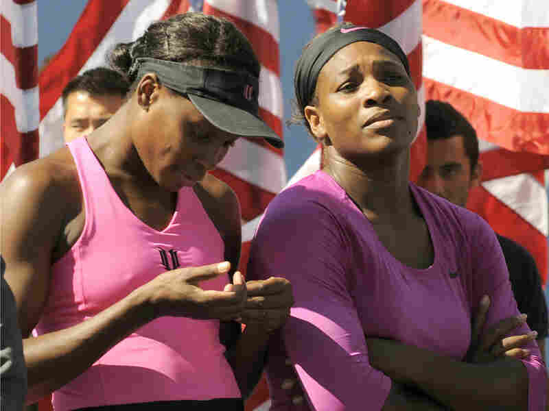 Serena (right) and Venus Williams wait to receive the winners' trophy.