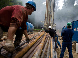 A drilling crew move a section of steel pipe at a natural gas well site near Bradford, Penn.