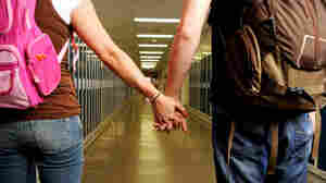 16: Students walk down a hall, holding hands. New programs help to end dating violence among teens