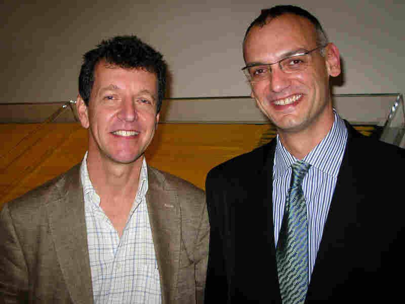 Simon Peers and Nicholas Godley stand in front of the gold tapestry.