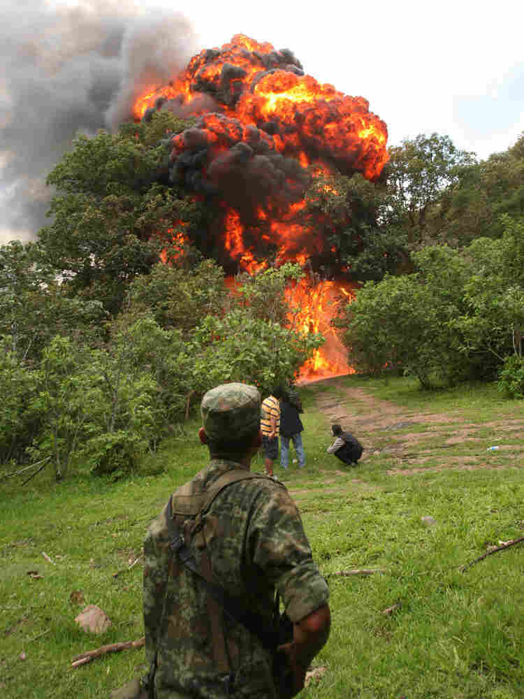 A soldier watches the burning of a clandestine methamphetamine laboratory.