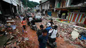 Residents walk through an area damaged earthquake in Padang