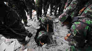 Wide: Soldiers look for survivors in rubble