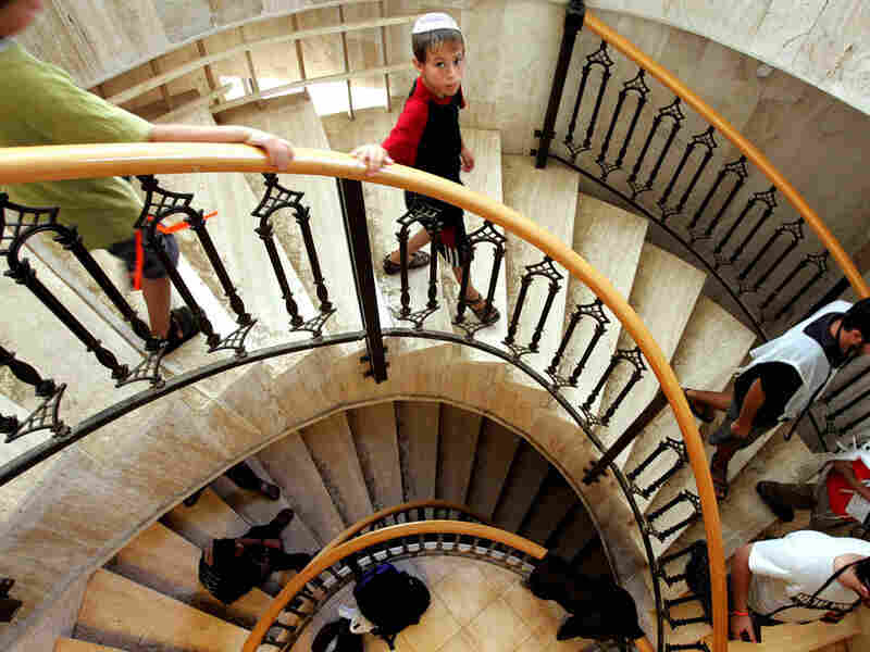 Jewish settlers walk down stairs in a synagogue.