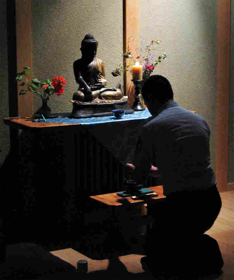 An Air Force Military Trainer kneels before the altar in the base's Buddhist chapel.