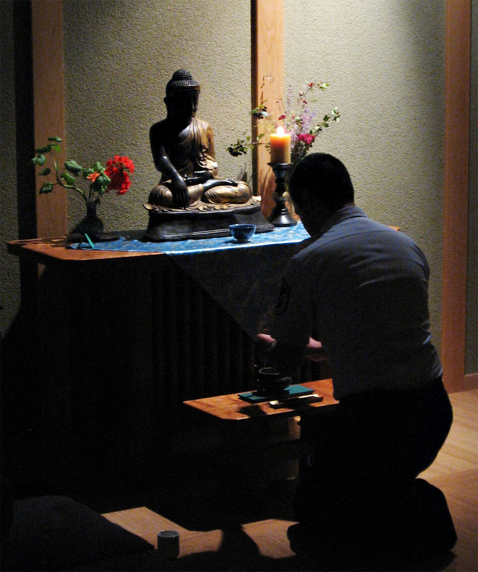 Steve Honda, an Air Force Academy military trainer, kneels before the altar in the base's Buddhist chapel.