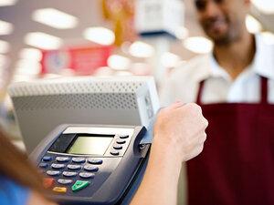 A shopper swipes a credit card at a store.
