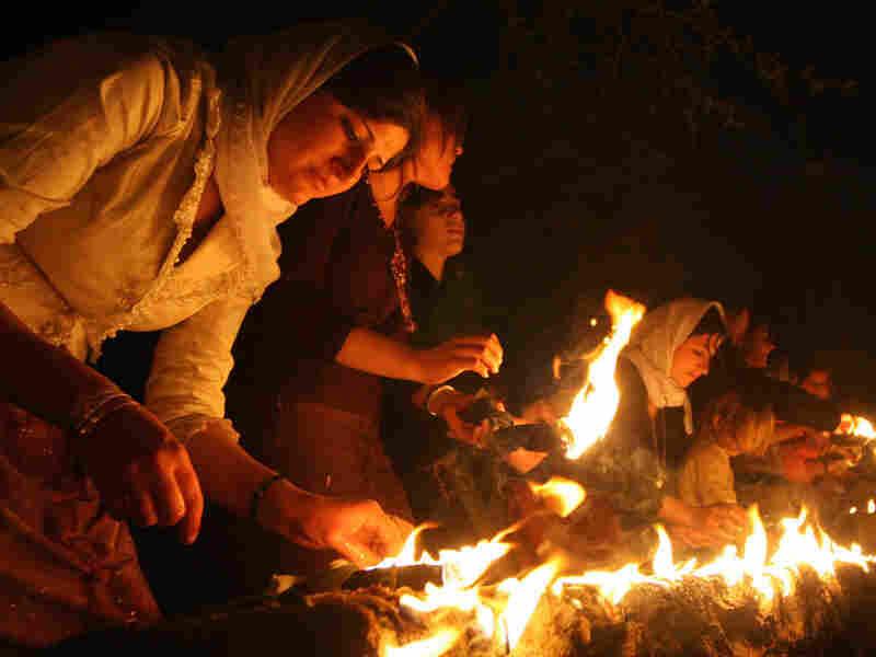 Iraqi Yazidis light candles outside Lalish temple in 2007.