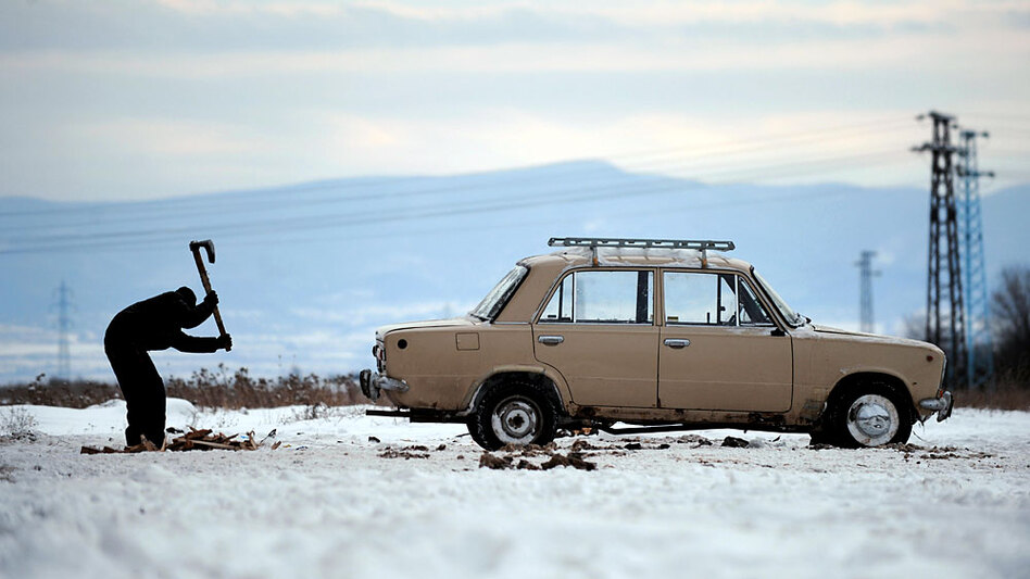 A boy chops wooden pallets next to a Russian-made Lada in the suburbs of Sofia, Bulgaria. Russian automaker AvtoVAZ has announced it will lay off 25,000 employees from its plant in Togliatti, where 1 in 7 residents is employed by the manufacturer.