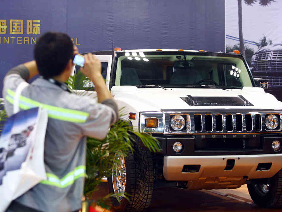 A visitor takes pictures of a Hummer SUV in June at a car show in Chongqing, China.