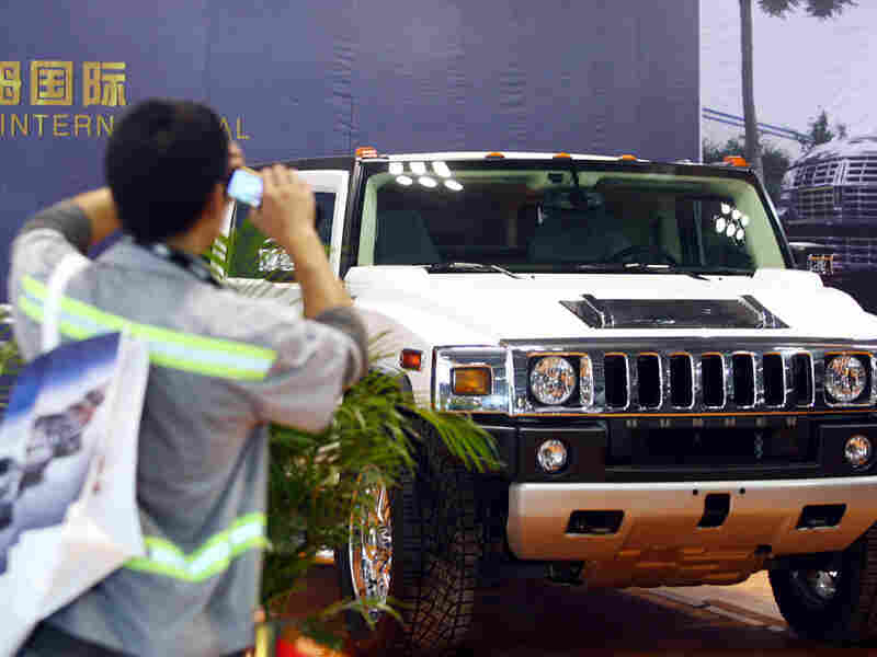 A visitor takes pictures of a Hummer SUV in June at a car show in Chon