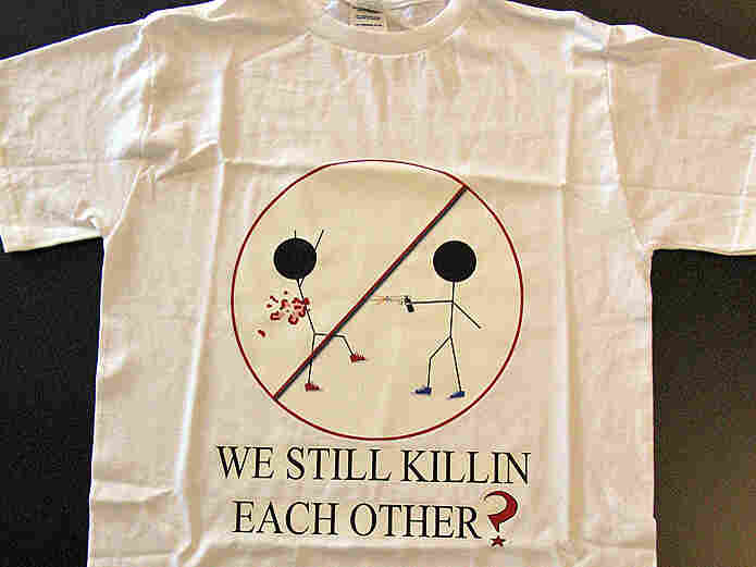 "A T-shirt reading ""We Still Killin Each Other?"""