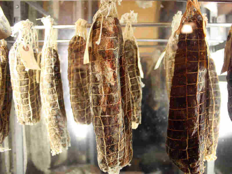 A row of cured meats hangs in the meat locker at Boccalone in San Francisco.