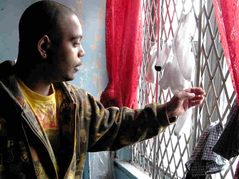 Luis Correa looks out broken windows of his apartment in the Bronx.