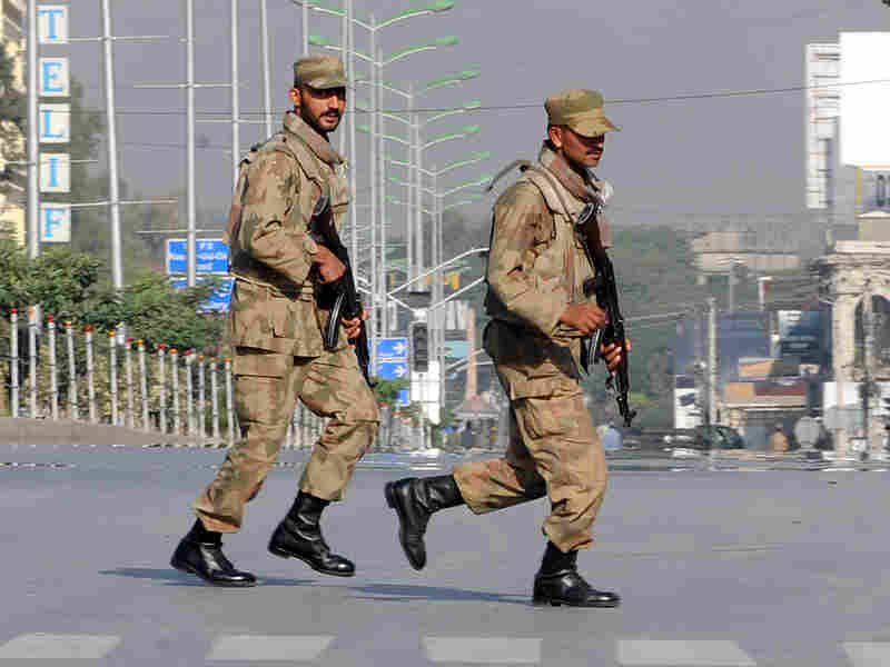 Pakistani troops take up positions at army headquarters Sunday in Rawalpindi