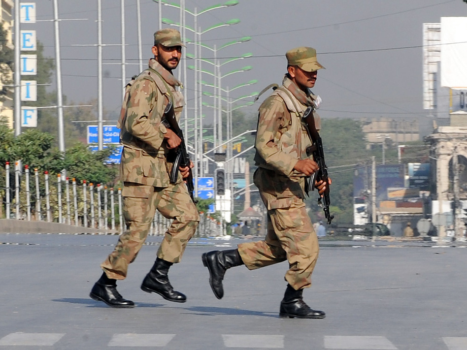 Pakistani troops take up positions at army headquarters during an encounter with militants Sunday in Rawalpindi. Pakistani troops stormed army headquarters to end a day-long hostage drama, freeing 39 people held by militants who brazenly struck at the heart of the country's military establishment.