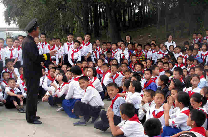 Schoolchildren listen to a lecture by one of the first North Koreans to board the USS Pueblo