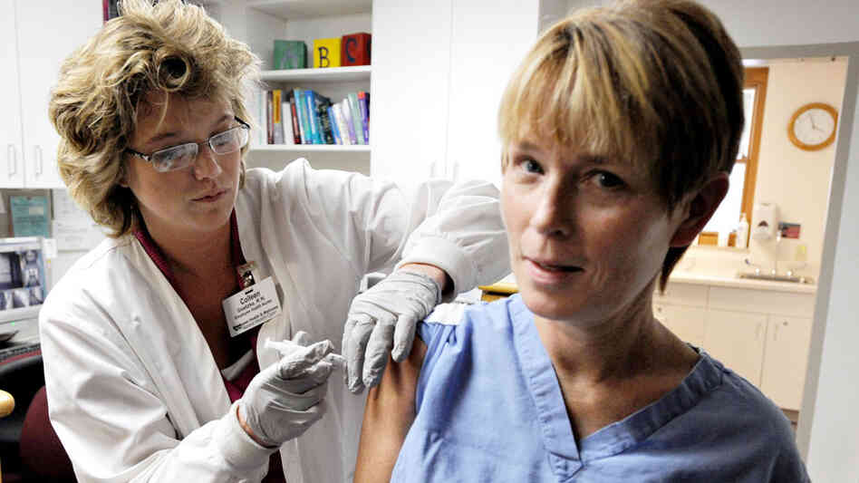 A wide-angle view of a nurse administering the swine flu vaccine into a patients upper arm.