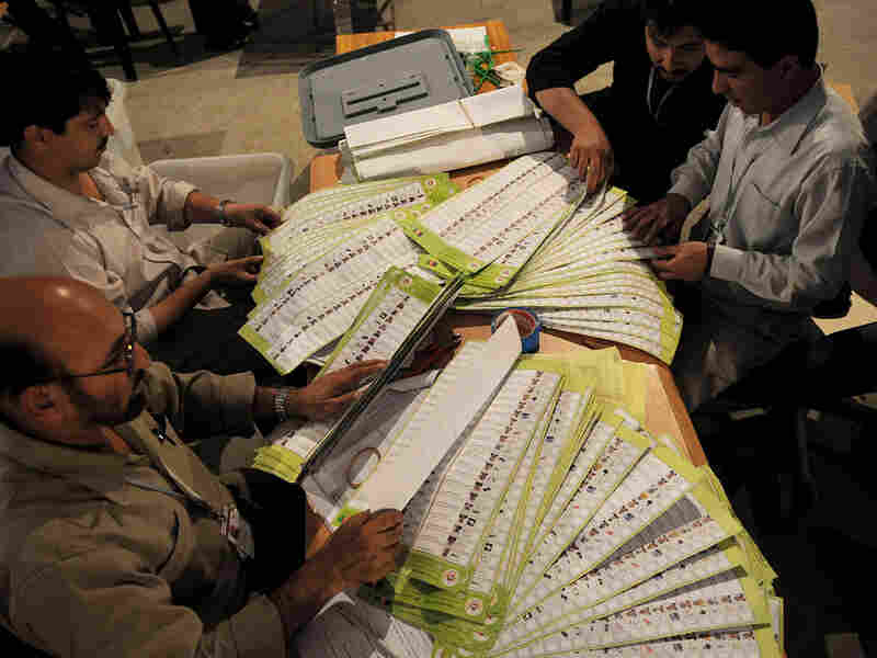 Election workers in Afghanistan audit suspect ballots.