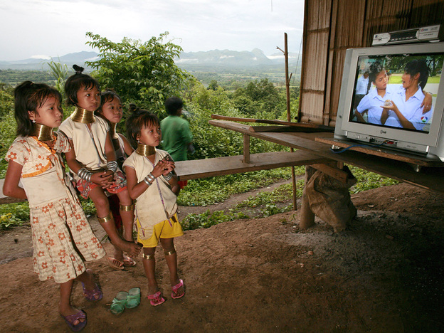 Young girls of the Long Neck Padaung hill tribe watch television in a small village in Chiang Dao, Thailand. By custom, girls in the tribe wear brass rings around their necks, beginning at age 5.