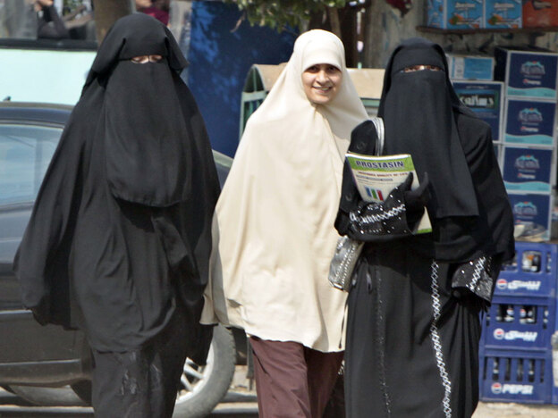 Egyptian students wearing the face-covering veil known as the niqab walk with another student in Cairo. Last week, Egypt's top Islamic cleric barred students from wearing face veils in the classrooms and dormitories of Sunni Islam's premier institute of learning, Al-Azhar. The decision appears to be part of a government campaign to crack down on overt manifestations of ultraconservative Islam in Egypt.