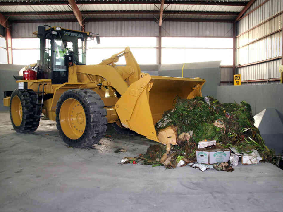 A front loader moves food waste in the Organics Annex.