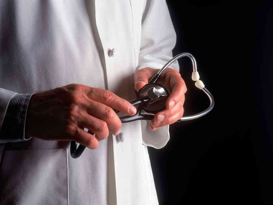 A doctor holds a stethoscope.