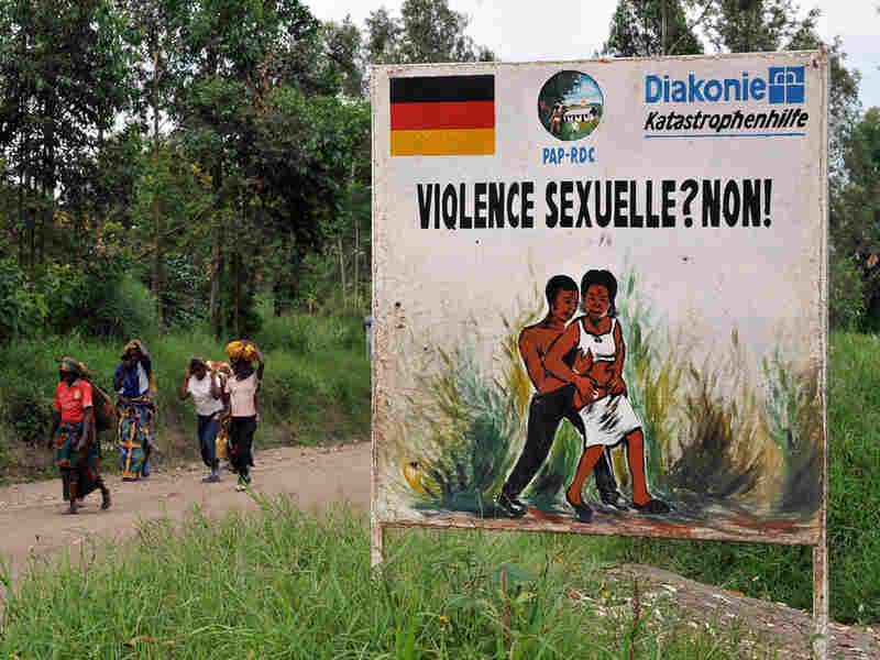 Congolese women walk past a sign opposing sexual violence in December 2008 in eastern Congo
