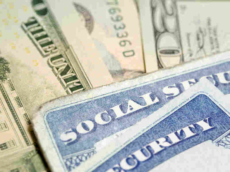 Social Security cards rest on a pile of cash