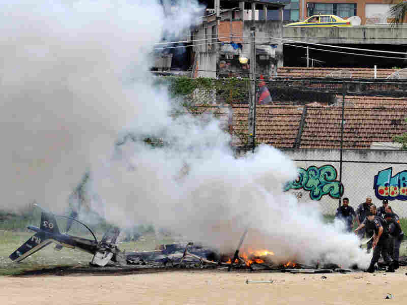 Police officers extinguish a fire from the wreckage of a police helicopter in Morro de Macacos slum.