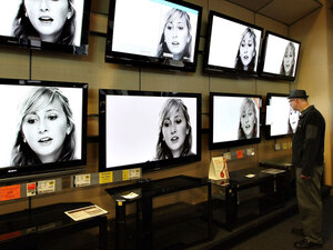 A customer looking at flat-panel televisions