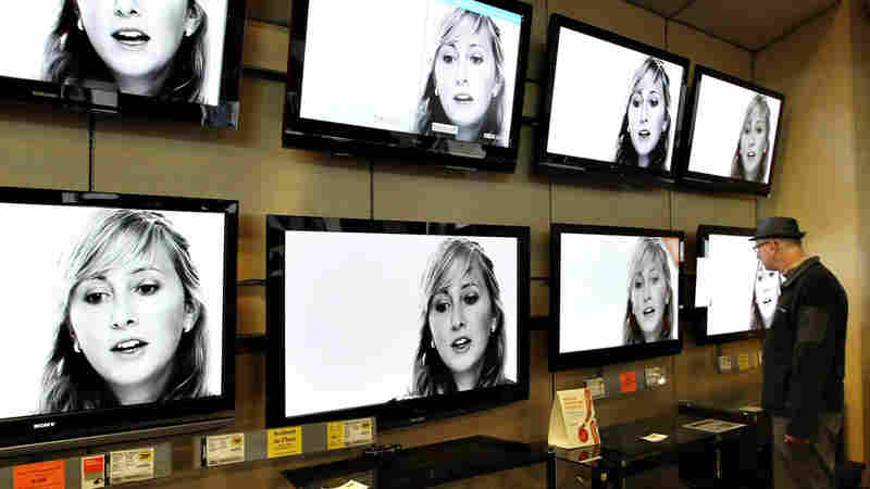 Wide: A customer looking at flat-panel televisions